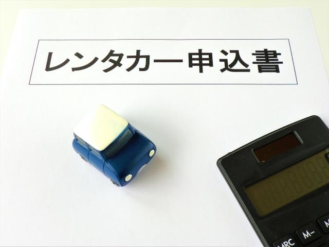 レンタカー申込書とおもちゃの車と電卓