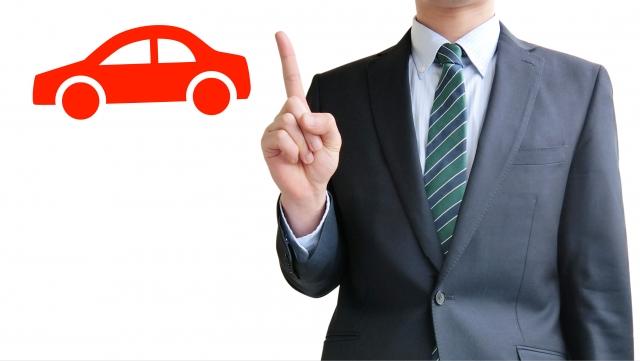 赤い車マークと指さしをするスーツの男性