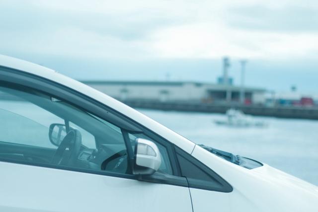 海辺をドライブする白い車