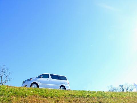 青空の下をドライブする白い車