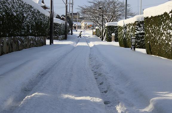 積雪した道路を雪カキをして横切る人