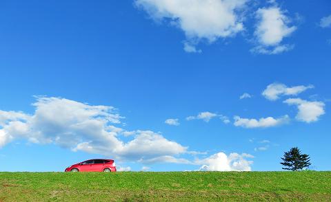 青空の下ドライブする赤い車