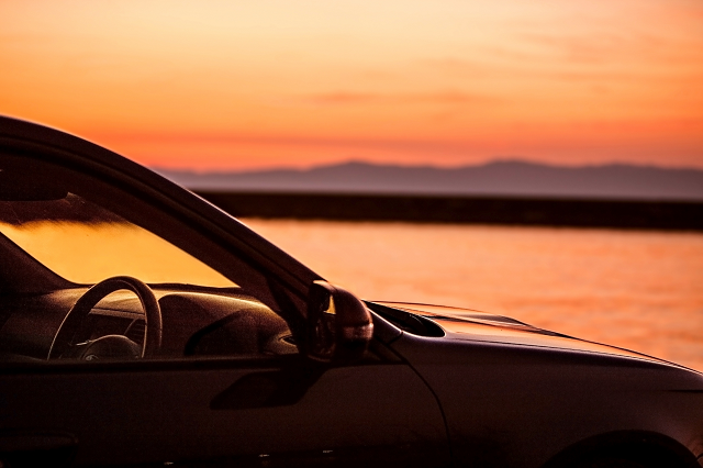 夕焼けに染まる湖畔と車