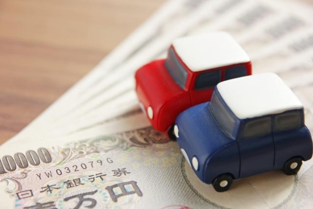 紙幣と赤と青のミニチュアの車