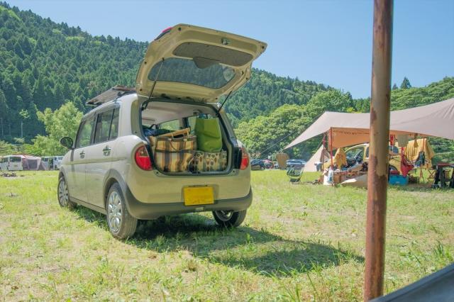 ラゲッジスペースに荷物が積まれたキャンプ場の軽自動車